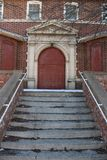 Uma escadaria rachada conduz a uma porta vermelha Foto de Stock