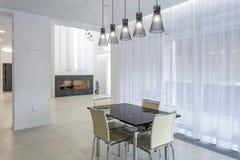 Uma escala de lâmpadas elegantes com a tabela de jantar no sótão interior brilhante imagens de stock
