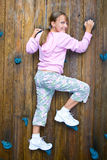 Uma escalada feliz da parede da rapariga. Fotos de Stock
