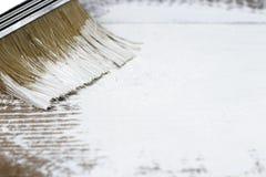 Uma escova com pintura branca em um fundo pintado de madeira, espaço da cópia, vista superior fotos de stock