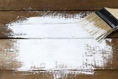 Uma escova com pintura branca em um fundo pintado de madeira, espaço da cópia, vista superior fotografia de stock royalty free