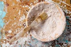 Uma escova em uma bacia com massa de vidraceiro secada em um cartão duro Foto de Stock