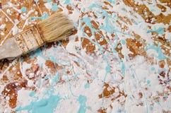 Uma escova em um cartão duro manchou com pintura Imagem de Stock