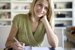 Uma escrita da mulher em sua agenda imagens de stock