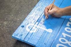 Uma escrita do homem assina a placa com uma escova das aquarelas no fundo do assoalho do cimento Pintura na placa de madeira na l fotos de stock royalty free