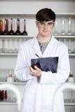 Uma escrita masculina do estudante da ciência em uma prancheta Foto de Stock Royalty Free