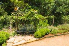 Uma escultura da borboleta acima de um balanço do jardim Foto de Stock