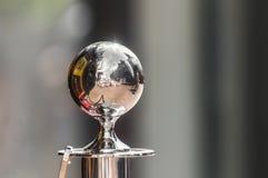 Uma esfera de alumínio contra um fundo obscuro foto de stock