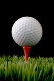 Uma esfera de golfe branca em um T no preto imagem de stock royalty free