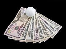 Uma esfera para o golfe encontra-se em notas do dólar Imagem de Stock Royalty Free
