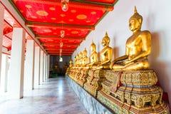 uma estátua de uma Buda assentada ao longo de uma parede em um templo Foto de Stock Royalty Free