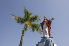 Uma estátua de Jesus Christ perto de uma palmeira verde contra um céu azul limpo foto de stock royalty free