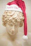 Uma estátua grega de mármore com chapéu de Santa Imagens de Stock