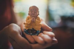 Uma estátua pequena da Buda nas mãos de uma mulher foto de stock