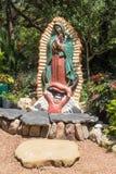 Uma estátua religiosa em um jardim que olhasse um tanto desvaneceu-se pelo sunl Fotos de Stock