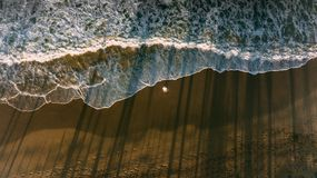 Uma estada dos homens na praia Reflexão da onda e da sombra das palmas escuro imagem de stock