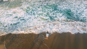 Uma estada dos homens na praia Reflexão da onda e da sombra das palmas luz foto de stock