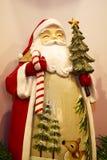 Uma estatueta da arte popular de Santa Claus que guarda um bastão da árvore e de doces fotografia de stock royalty free