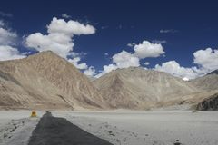 Uma estrada através da cama de rio seca e sandunes no vale Ladakh de Nubra Imagens de Stock