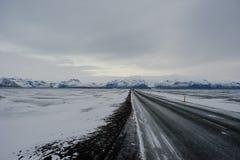 Uma estrada através da neve em Islândia Imagem de Stock