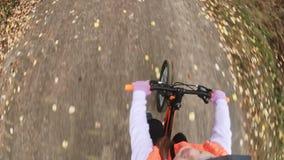 Uma estrada caucasiano da bicicleta dos passeios das crianças no parque do outono O ciclo alaranjado preto da equitação da menina filme
