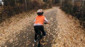Uma estrada caucasiano da bicicleta dos passeios das crianças no parque do outono O ciclo alaranjado preto da equitação da menina imagem de stock royalty free
