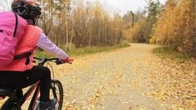 Uma estrada caucasiano da bicicleta dos passeios das crianças no parque do outono O ciclo alaranjado preto da equitação da menina vídeos de arquivo