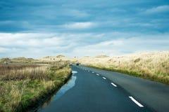Uma estrada com carros através de um céu tormentoso foto de stock royalty free