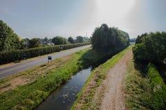Uma estrada conduz a uma área residencial quieta da vizinhança com as casas holandesas tradicionais do estilo durante o por do so fotografia de stock royalty free