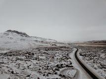 Uma estrada curvy através da neve em Islândia Fotos de Stock Royalty Free