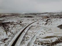 Uma estrada curvy através da neve em Islândia Imagem de Stock Royalty Free