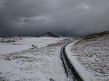 Uma estrada curvy através da neve em Islândia Fotografia de Stock