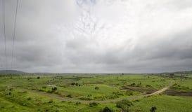 Uma estrada curvy através dos pastores verdes Foto de Stock