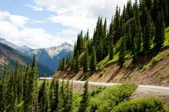 Uma estrada curvy entre montanhas tampadas neve. Fotos de Stock Royalty Free