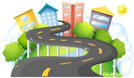 Uma estrada da curva que vai à cidade com construções altas Foto de Stock Royalty Free