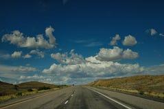 Uma estrada disparou com algumas nuvens agradáveis ao viajar através de Utá ou de Colorado Foto de Stock Royalty Free