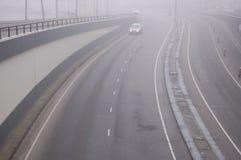 Uma estrada enevoada com um carro   Imagens de Stock