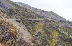 Uma estrada pequena da montanha viaja através da terra de Alaska imagens de stock royalty free