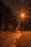Uma estrada pequena em uma floresta iluminou-se por lanternas Foto de Stock Royalty Free