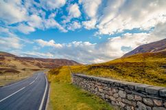 Uma estrada principal típica através de um vale escocês que conduz com Fotografia de Stock