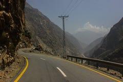 Uma estrada que carrega às montanhas e aos vales com um céu completo das nuvens Foto de Stock