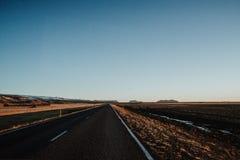 Uma estrada reta através de Islândia Fotos de Stock