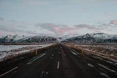 Uma estrada reta através de Islândia Imagens de Stock Royalty Free