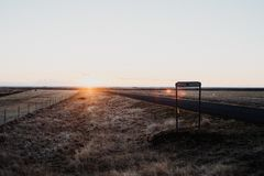 Uma estrada reta através de Islândia no por do sol Foto de Stock Royalty Free