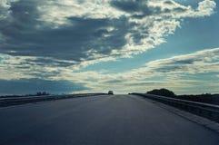 Uma estrada rodoviária asfaltada com um carro contra o céu com nuvens fotos de stock
