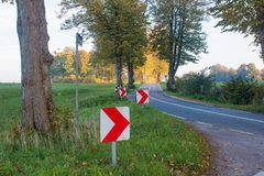 Uma estrada secundária com árvores e curvaturas e sinais de estrada fotografia de stock royalty free