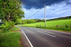 Uma estrada vazia no campo Imagens de Stock Royalty Free