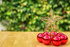 Uma estrela bonita do Natal cercada por algumas bolas vermelhas do Natal Imagens de Stock