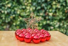 Uma estrela bonita do Natal cercada por muitos bola vermelha do Natal Fotos de Stock Royalty Free