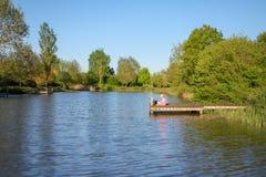 Uma estudante da criança de 7 anos está sentando-se em um cais por um lago e está guardando-se uma vara de pesca na água foto de stock